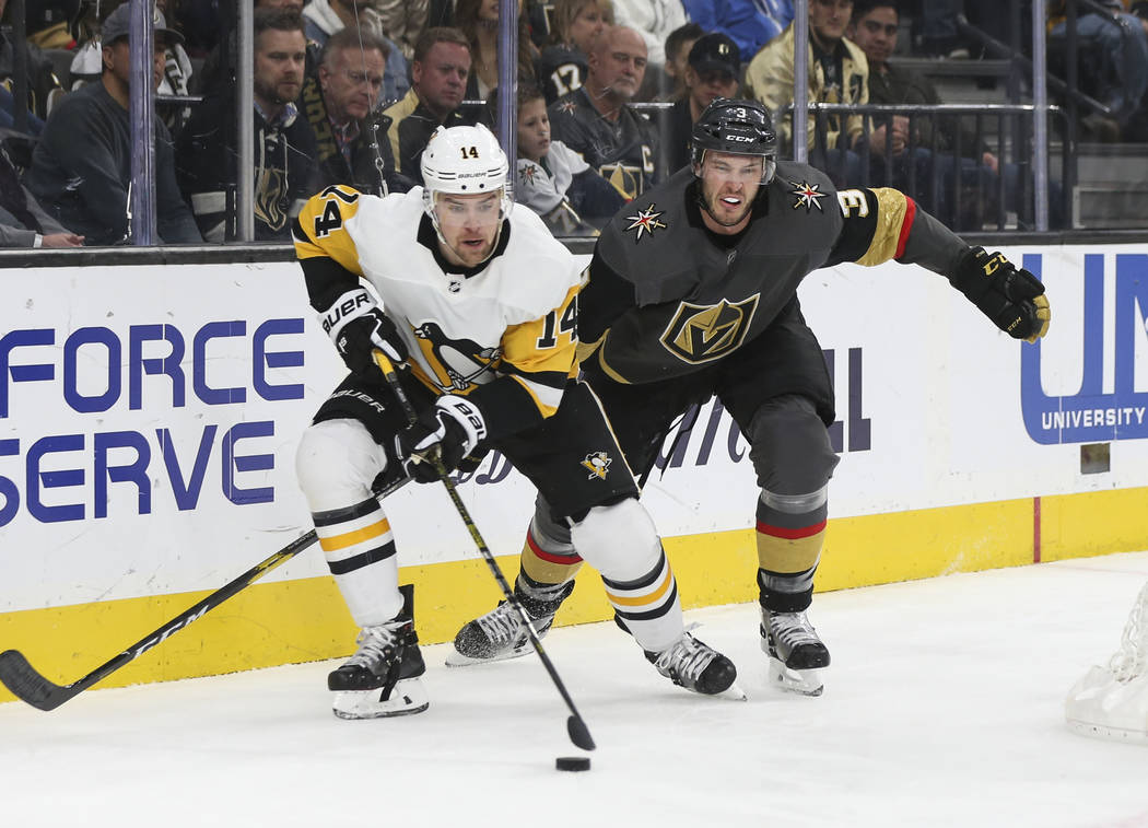 El ala izquierda de los Pittsburgh Penguins, Tanner Pearson (14), mueve el disco frente al defensor de los Golden Knights, Brayden McNabb (3), durante el segundo período de un juego de hockey de ...