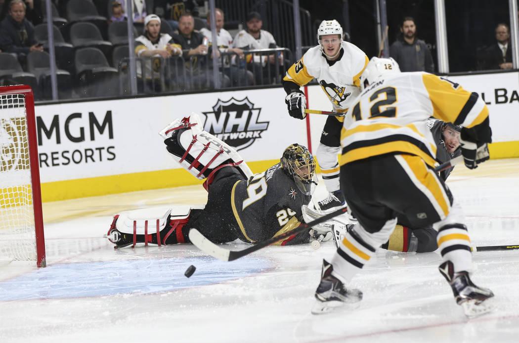 El centro de los Pittsburgh Penguins, Dominik Simon (12), envía el disco a la red al lado del portero de los Golden Knights Marc-André Fleury (29) durante el segundo período de un juego de hock ...