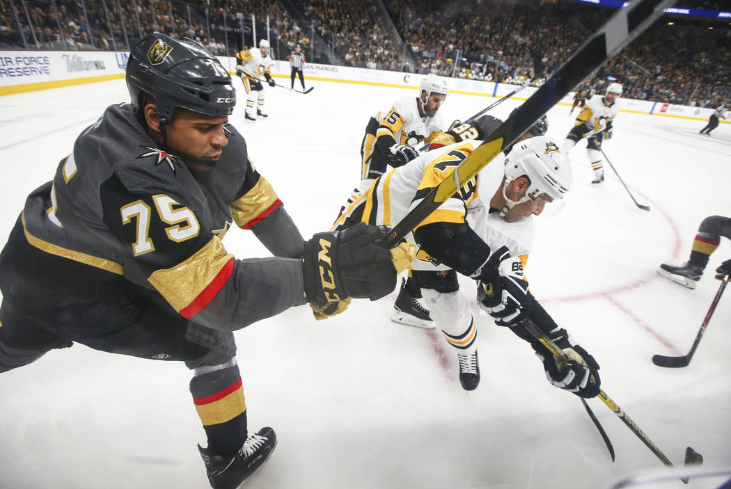 El ala derecha de los Caballeros Dorados, Ryan Reaves (75), y el defensa de los Pittsburgh Penguins, Jack Johnson (73), luchan por el disco durante el primer período de un juego de hockey de la N ...