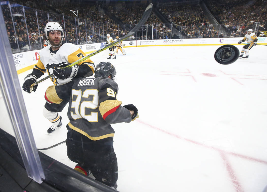 El centro de los Pittsburgh Penguins, Matt Cullen (7), envía al puck al ala izquierda de los Golden Knights, Tomas Nosek (92), durante el tercer período de un juego de hockey de la NHL en T-Mobi ...