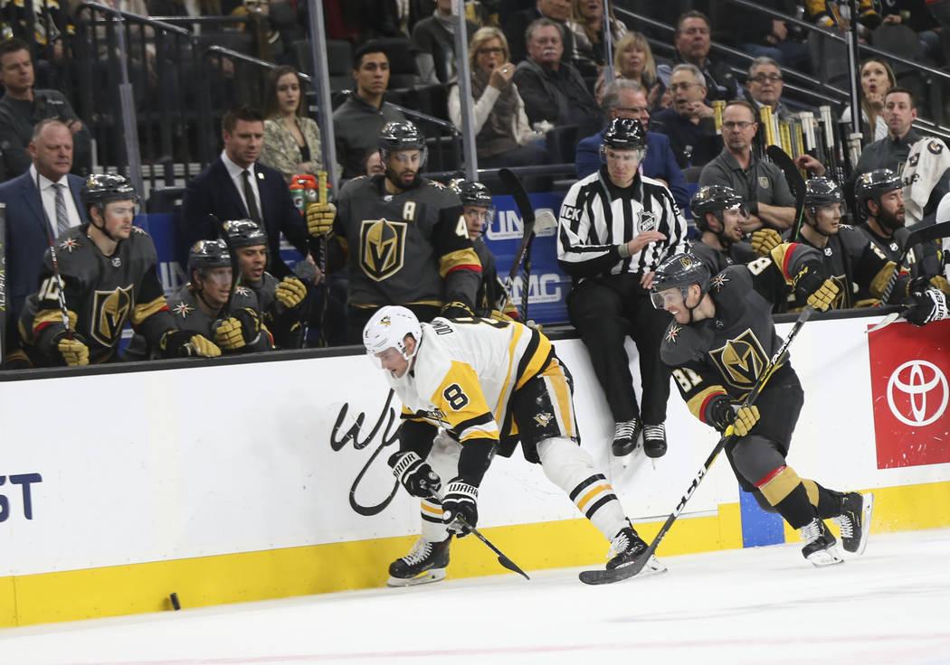 El centro de Golden Knights, Jonathan Marchessault (81), persigue al el puck junto al defensa Brian Dumoulin (8) de los Pittsburgh Penguins durante el tercer período de un juego de hockey de la N ...
