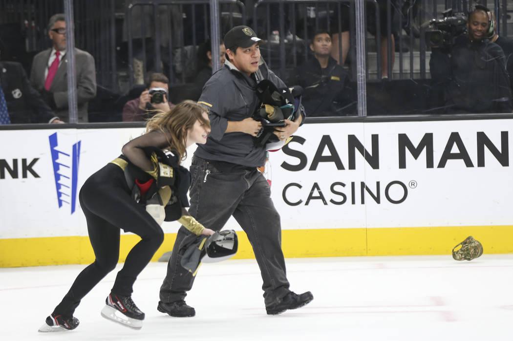 Miembros del personal de hielo de los Golden Knights recogen los sombreros que se lanzaron para celebrar un 'hat trick' de Jonathan Marchessault, que no aparece en la foto, durante el tercer perí ...