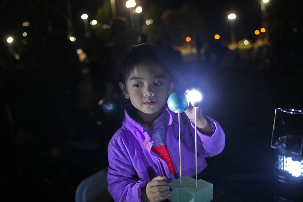 Raema Macababbad, de 3 años, participa en un proyecto para mostrar a los niños cómo funciona el eclipse lunar organizado por la Sociedad Astronómica de Las Vegas en el estacionamiento de la Un ...