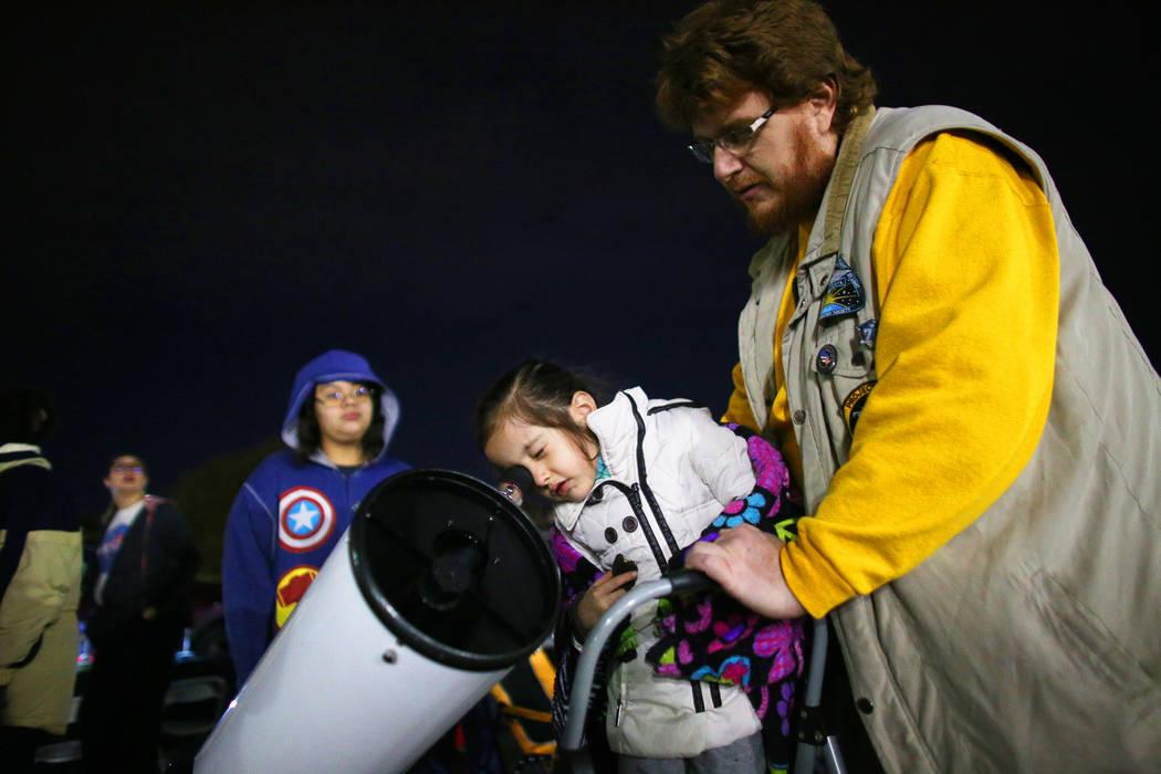 Francisco Silva, vicepresidente del programa de extensión educativa de la Sociedad Astronómica de Las Vegas, ayuda a Catherine Lawrence, de 5 años, a ver la luna en la observación del eclipse ...