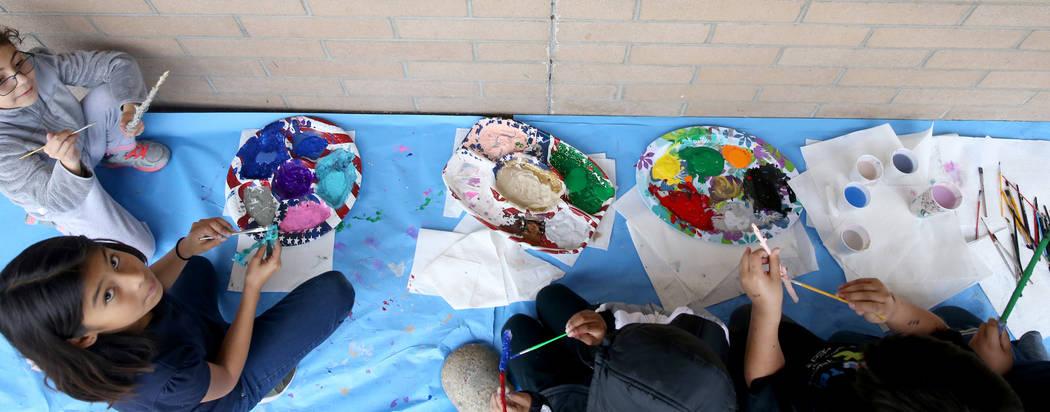 Los estudiantes, incluyendo a Adelyne Gómez, a la izquierda, y Nathalie Ibarra-Lobato, segunda a la izquierda, pintan varitas mágicas durante una lección de lectura con el tema de Harry Potter ...