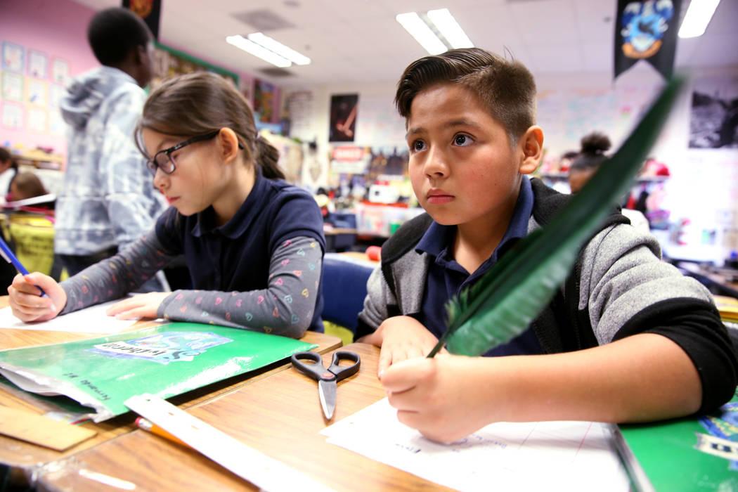 Arturo Vázquez Robledo usa una pluma durante una lección de lectura con el tema de Harry Potter en la clase de cuarto grado de Kathryn Faulkner en la escuela primaria Tate en Las Vegas el jueves ...