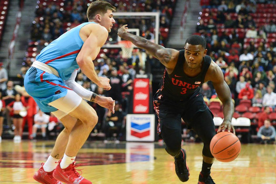 El defensa de los Rebels de la UNLV Amauri Hardy (3), driblea el balón al pasar a Dane Kuiper (14) de los Lobos de Nuevo México durante la primera mitad del juego de baloncesto de la NCAA contra ...