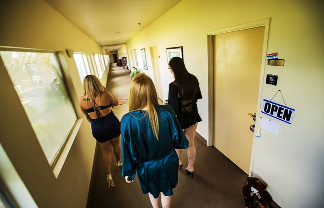 ARCHIVO.- Las trabajadoras sexuales Perla, a la izquierda, Erin y Emma, sus nombres escénicos, caminan por el pasillo en Sheri's Ranch, un centro de entretenimiento para adultos en Pahrump, Nevad ...