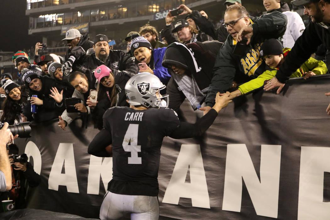 El mariscal de campo de los Oakland Raiders, Derek Carr (4), se reúne con los fans en el campo del Coliseo del Condado de Oakland-Alameda luego de la victoria del equipo sobre los Broncos de Denv ...