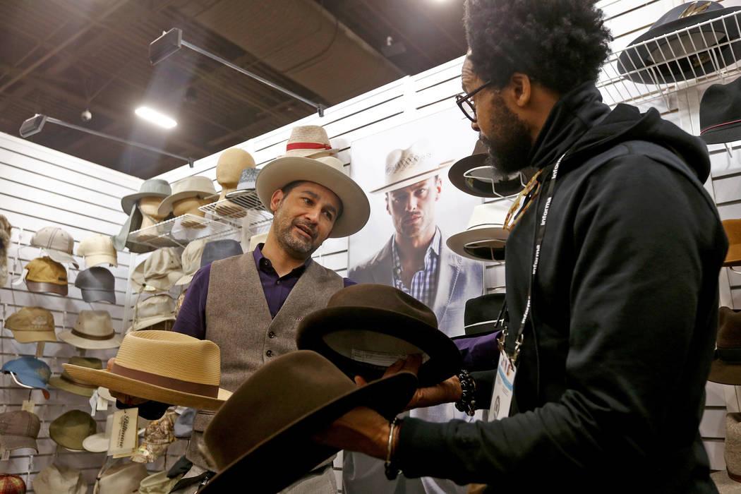 Victor Cornejo le muestra a Kevin Scott sombreros diferentes para comprar en el stand de Biltmore Hats en la feria de moda MAGIC en el Mandalay Bay Convention Center en Las Vegas, el miércoles 6 ...
