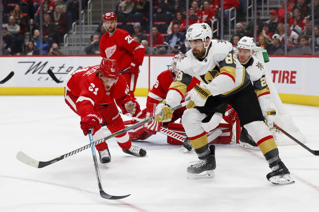 El ala derecha de los Golden Knights de Las Vegas, Alex Tuch (89), pasa mientras el centro de los Detroit Red Wings, Jacob de la Rose (61), defiende en el primer período de un juego de hockey de ...