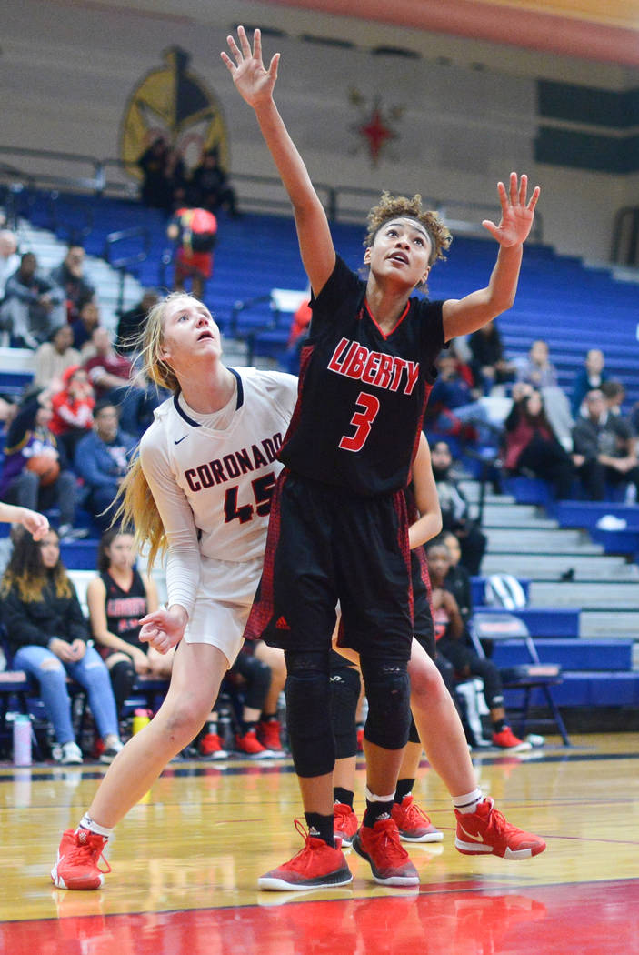 La senior de Liberty, Journie Augmon (3) lucha por la posición con Haley Morton (45), senior de Coronado, mientras espera un rebote en el segundo cuarto de un juego entre Coronado High School y L ...