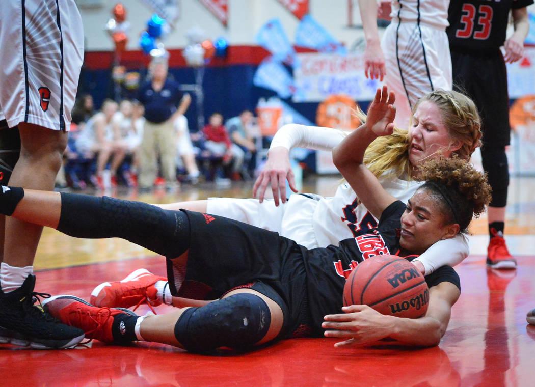 La estudiante senior de Liberty, Journie Augmon (3), lucha por la posesión del balón suelto con la estudiante senior de Coronado, Haley Morton (45), mientras esperaba un rebote en el segundo cua ...