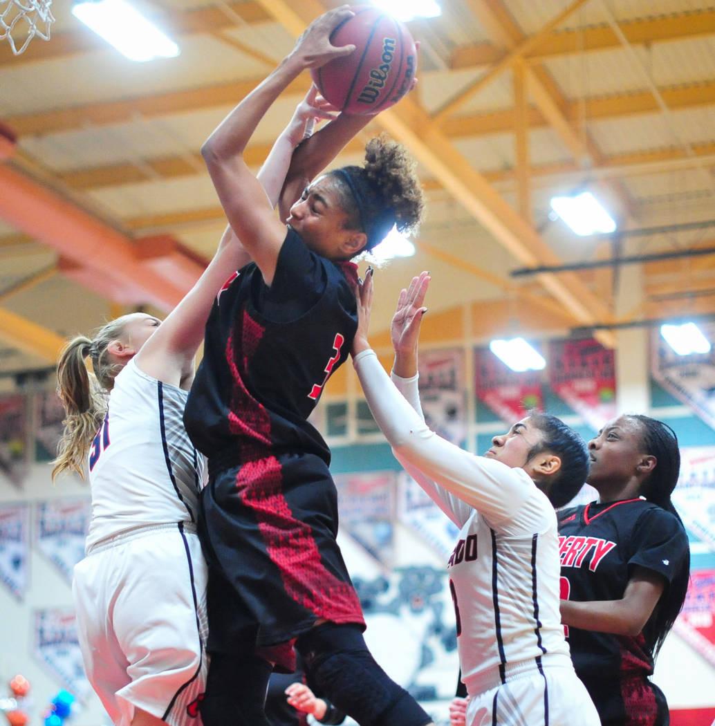 La senior de Liberty, Journie Augmon (3), derriba un rebote sobre la senior de Coronado, Kaitlyn Hamlin (31), en el cuarto trimestre de un juego entre Coronado High School y Liberty High School en ...
