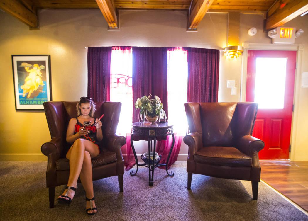 La prostituta Brooklyn Moore, a la izquierda, usa su teléfono mientras espera a los clientes en el burdel Love Ranch en Crystal, justo al norte de Pahrump, el viernes 20 de julio de 2018. Chase S ...