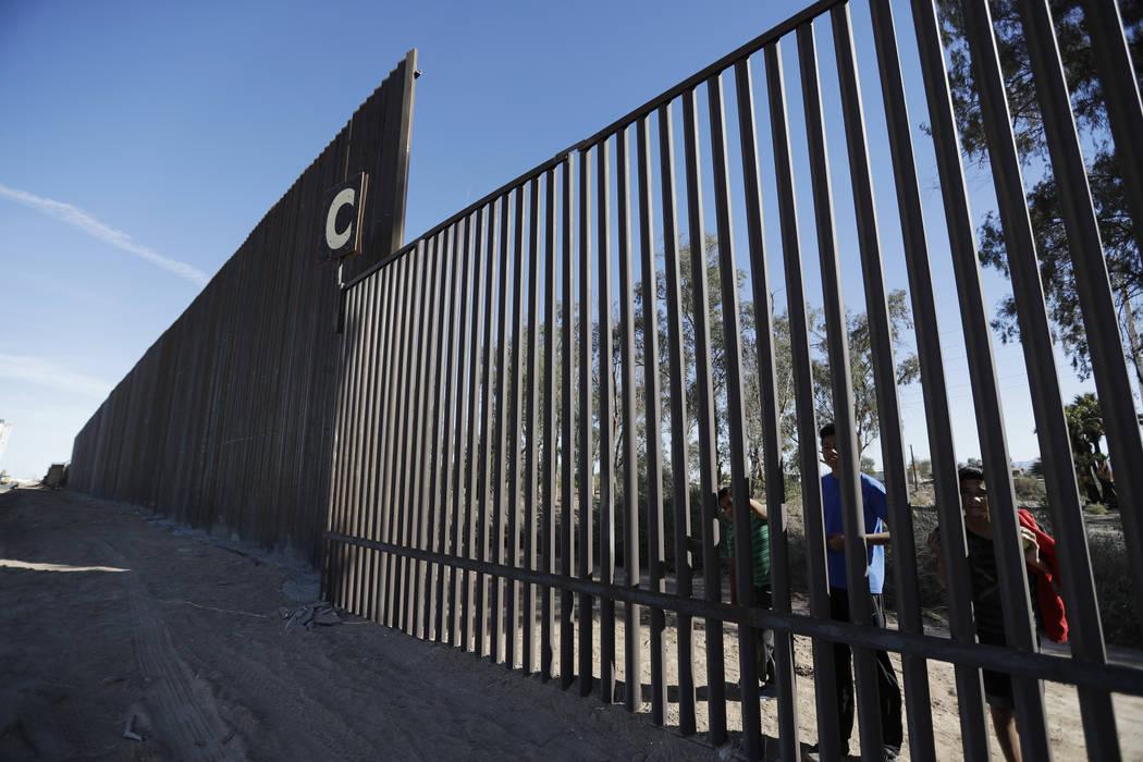 ARCHIVO: en esta foto de archivo del 5 de marzo de 2018, los niños miran a través de una sección más antigua de la estructura de la frontera de Mexicali, México, junto a una sección más alt ...