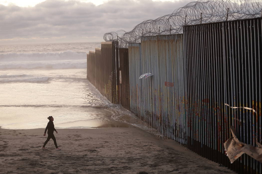 Una mujer camina en la playa junto al muro fronterizo cubierto con alambre de púas en Tijuana, México, en enero de 2019. (Foto de AP / Gregory Bull)