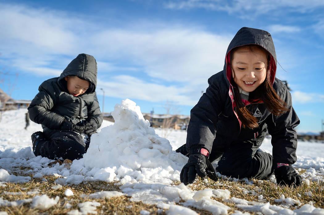 Tenley Chou, de 5 años, derecha, alcanza un montón de nieve mientras construye un muñeco de nieve con su hermano Jace Chou, de 7 años, izquierda, en Fox Hill Park en el área de Summerlin en L ...