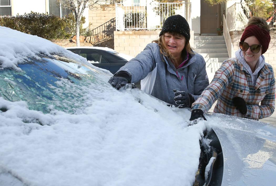 Rhonda Davis, a la izquierda, de San Diego y su hija Meagan Hoyt de Las Vegas retiran la nieve del automóvil de Davis en Summerlin el lunes 18 de febrero de 2019, en Las Vegas. (Bizuayehu Tesfaye ...