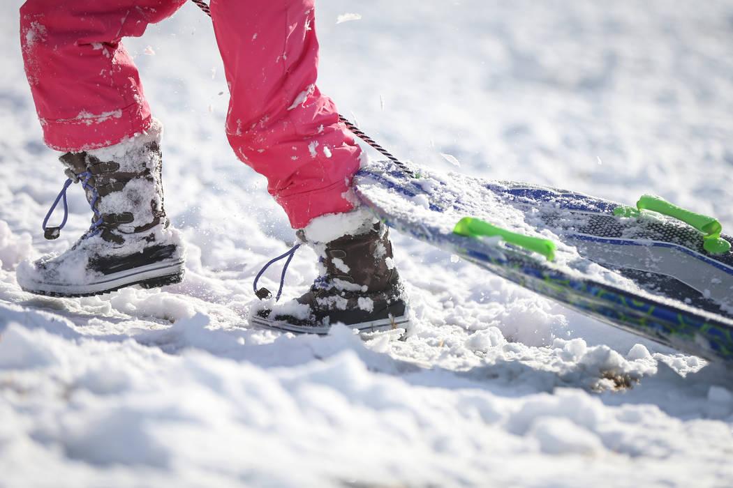 Nora Petronzi, de 8 años, camina por una colina cubierta de nieve con su trineo en Fox Hill Park en el área de Summerlin en Las Vegas, el lunes 18 de febrero de 2019. (Caroline Brehman / Las Veg ...