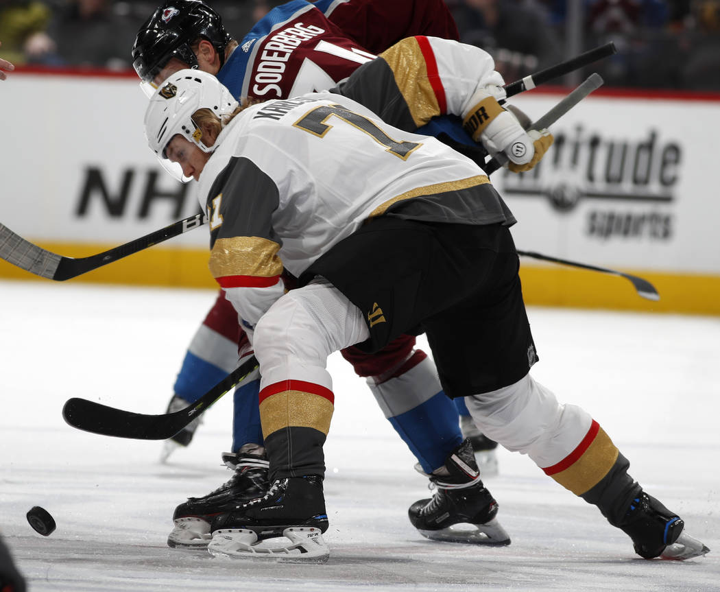 El centro William Karlsson de los Vegas Golden Knights, frente, lucha por el control del disco con el centro de los Colorado Avalanche, Carl Soderberg, en el primer período de un juego de hockey ...