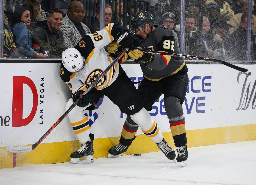El defensa de los Boston Bruins, Kevan Miller (86) y el ala izquierda de los Golden Knights, Tomas Nosek (92), luchan por el disco durante el primer período de un juego de hockey de la NHL en T-M ...