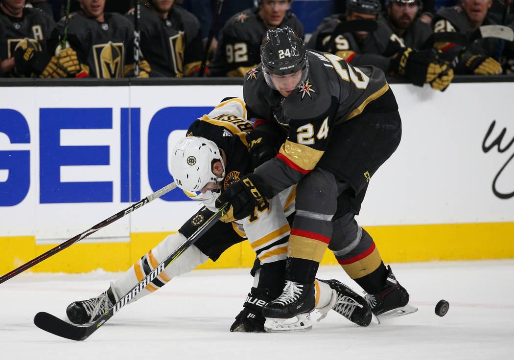 El ala izquierda de los Boston Bruins, Jake DeBrusk (74) y el centro de los Vegas Golden Knights, Óscar Lindberg (24), luchan por el disco durante el primer período de un juego de hockey de la N ...