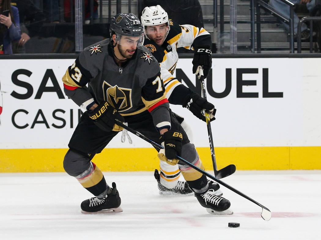 Brandon Pirri (73), centro de los Golden Knights de Las Vegas, se mueve con el disco mientras está custodiado por Patrice Bergeron (37) de los Boston Bruins durante el primer período de un juego ...