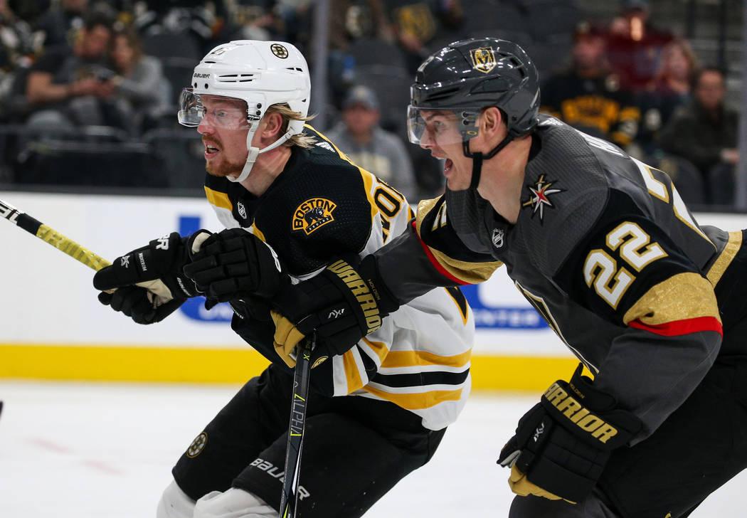 El centro de los Boston Bruins, Joakim Nordstrom (20) y Nick Holden (22) de los Vegas Golden Knights, avanzan hacia el disco durante el segundo período de un juego de hockey de la NHL en T-Mobile ...
