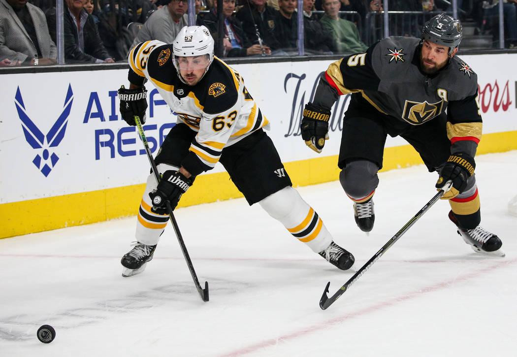 El ala izquierda de los Bruins de Boston, Brad Marchand (63), patina hacia el disco mientras el defensa de los Golden Knights de Las Vegas, Deryk Engelland (5) se queda atrás durante el segundo p ...