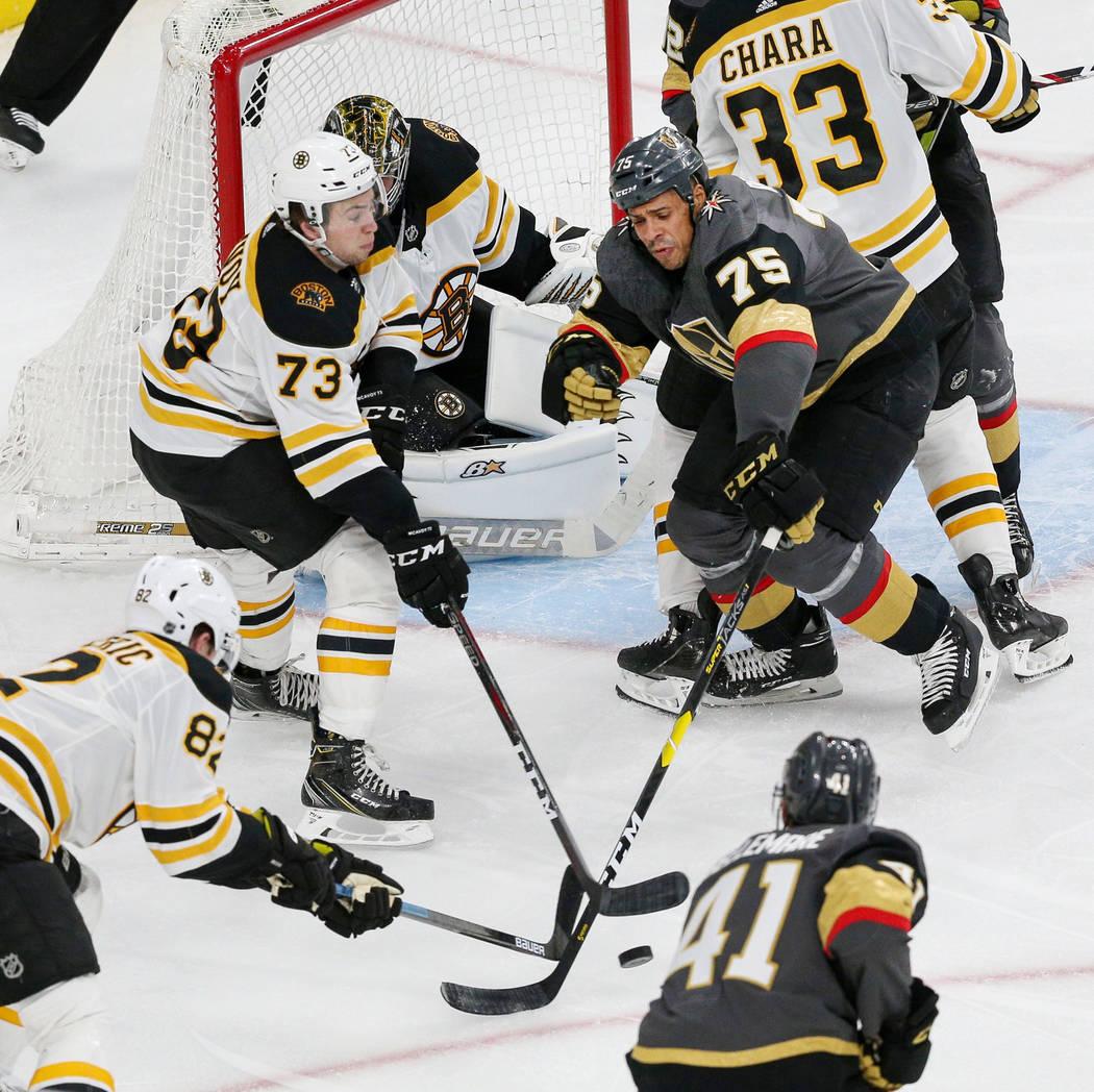 El centro de los Boston Bruins, Trent Frederic (82), el defensa, Charlie McAvoy (73) y el ala derecha de los Golden Knights de Las Vegas, Ryan Reaves (75), luchan por el disco durante el tercer pe ...