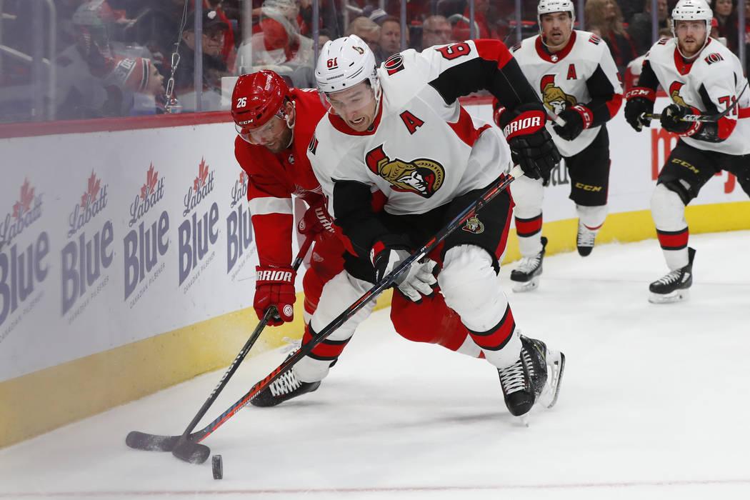 El ala derecha de los Senators de Ottawa, Mark Stone (61), lucha con el ala roja de los Detroit Red Wings, Thomas Vanek (26), por el disco en el segundo período de un juego de hockey de la NHL el ...