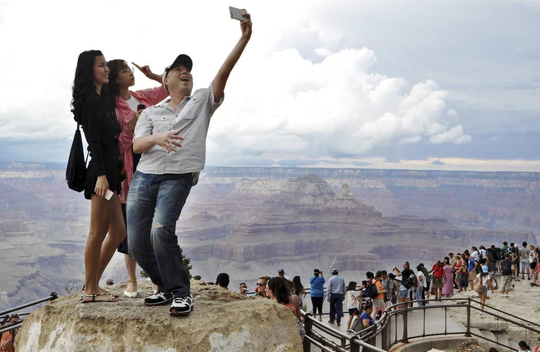 En esta foto de archivo del 2 de agosto de 2015, los turistas Joseph Lin, Ning Chao, centro, y Linda Wang, izquierda, posan para una selfie a lo largo del borde sur del Parque Nacional del Gran Ca ...