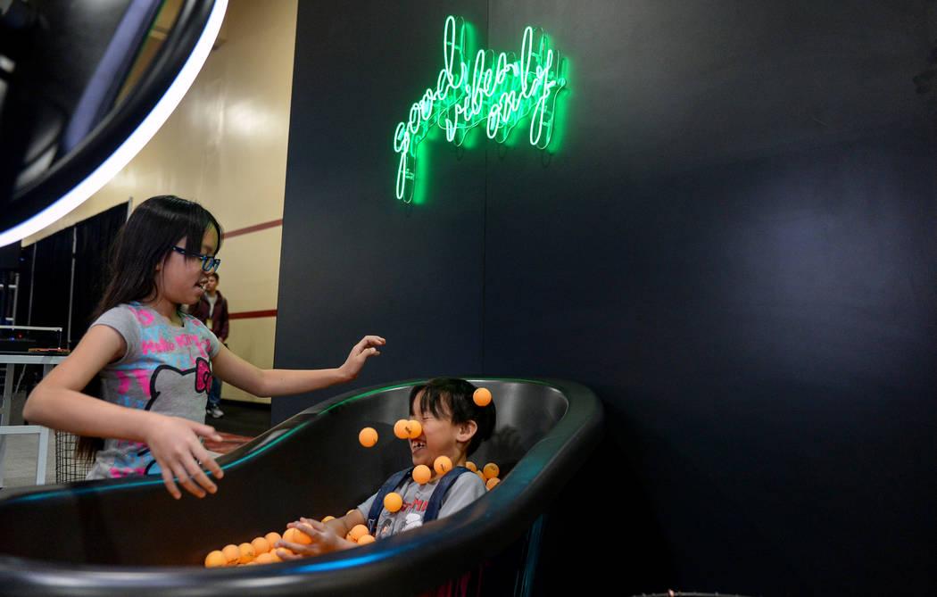 Delilah Crisóstomo, de 10 años, lanza pelotas de ping pong a su hermano, Davis Crisóstomo, de 8 años, en el stand de Simple Booth en la exposición Photo Booth en el South Point Hotel and Casi ...