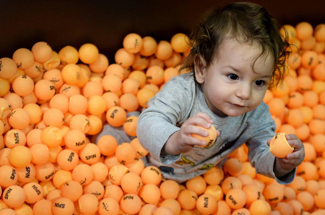 Atlas Varela, de 13 meses, se sienta en una bañera llena de pelotas de ping pong en el stand de Simple Booth en el Photo Booth Expo en el South Point Hotel and Casino en Las Vegas, el martes 26 d ...