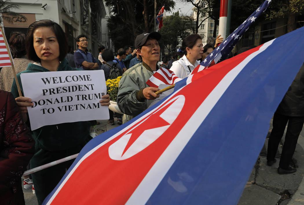 La gente sostiene pancartas y banderas de Estados Unidos y Corea del Norte fuera del hotel Metropole donde el presidente Donald Trump y el líder norcoreano Kim Jong Un cenarán en Hanoi, Vietnam, ...