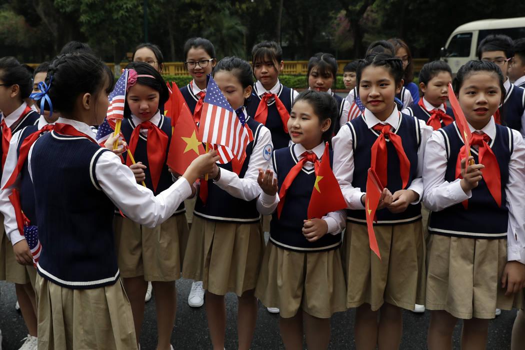 Se entregan banderas estadounidenses a los niños antes de que llegue el presidente Donald Trump para reunirse con el presidente vietnamita Nguyen Phu Trong en el Palacio Presidencial, el miércol ...
