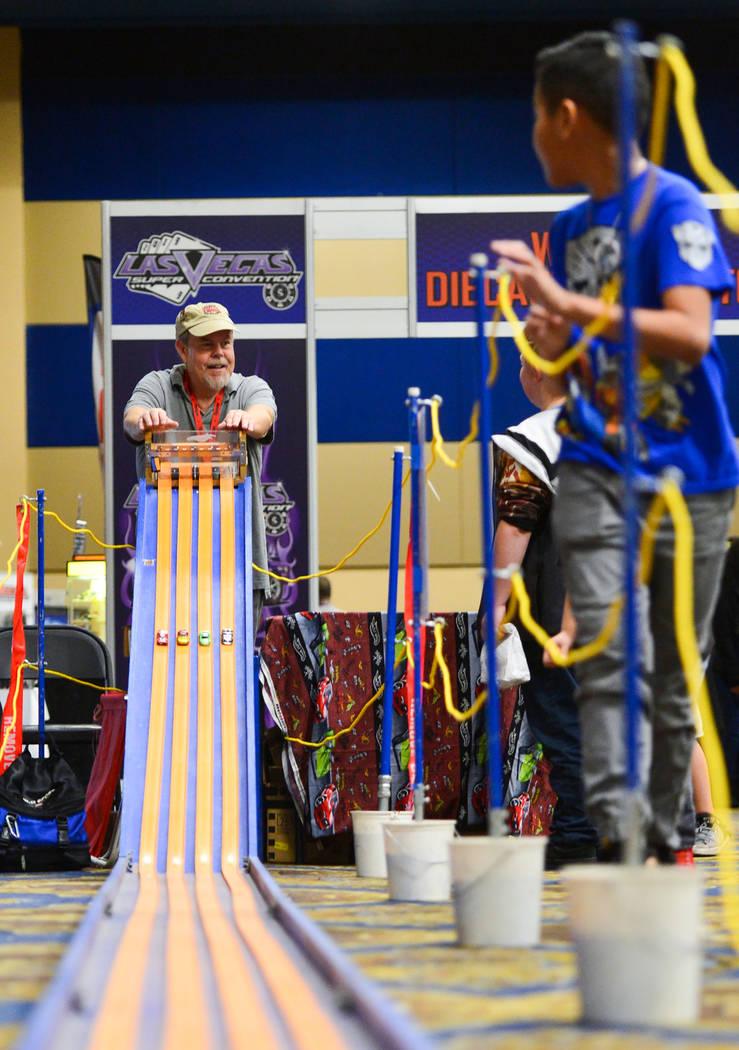 Los niños corren a lo largo de la pista de Hot Wheels cuesta abajo cuando Matt Marion, a la izquierda, abre la puerta para comenzar una carrera en Las Vegas Toy and Comic Convention en Westgate R ...