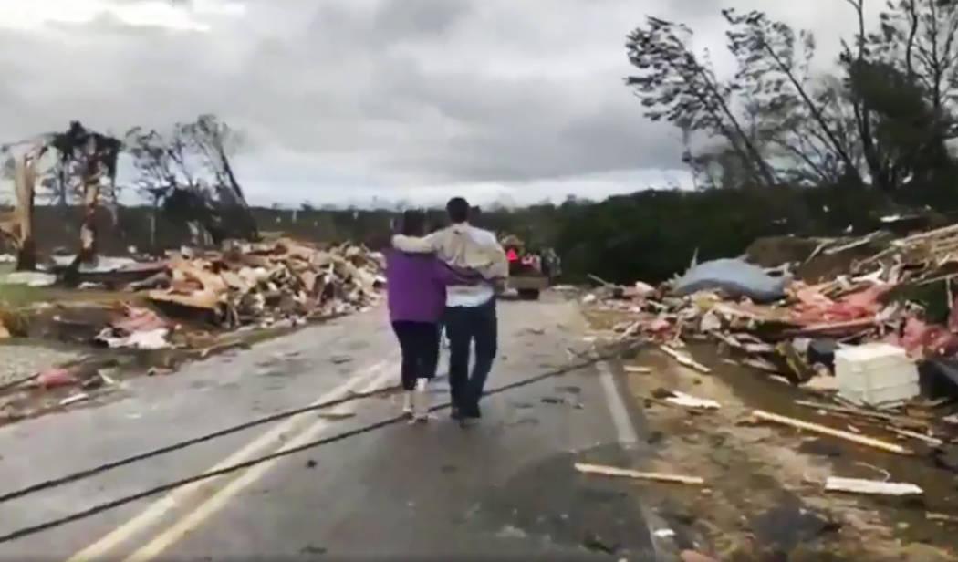 La gente camina entre escombros en el Condado de Lee, Alabama, después de lo que parecía ser un tornado que golpeó el área el domingo 3 de marzo de 2019. Las tormentas severas destruyeron casa ...