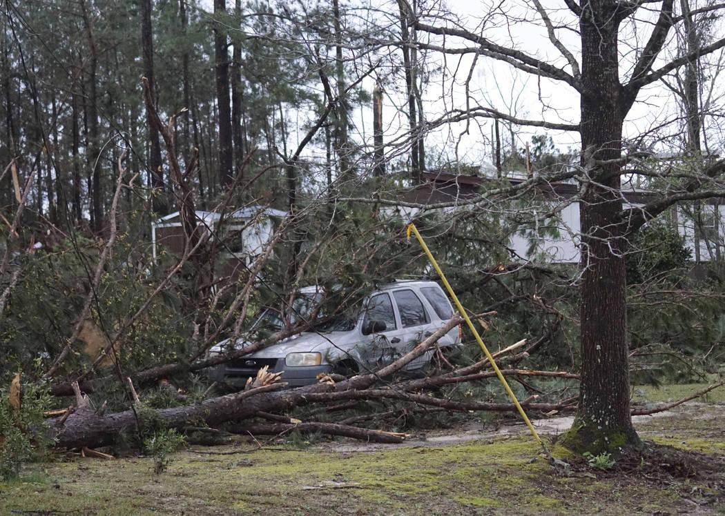 Un vehículo es atrapado debajo de árboles derribados a lo largo de Lee Road 11 en Beauregard, Alabama, el domingo 3 de marzo de 2019, luego de que un poderoso sistema de tormentas atravesara el ...