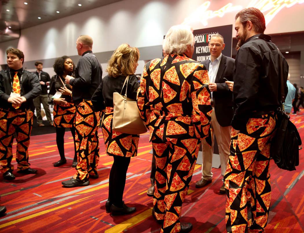 Pat Spaulding de Spaulding & Associates, Inc., de Brighton Michigan, en traje, habla con su equipo de Cheese Guys en la Exposición Internacional de Pizza en el Centro de Convenciones de Las Vegas ...