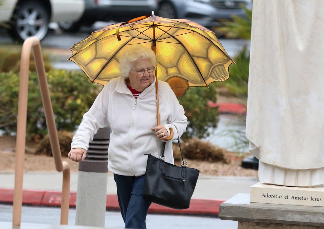 Una mujer sostiene un paraguas para protegerse de la lluvia mientras se dirige a la iglesia católica St. Viator el miércoles, marzo. 6, 2019, en Las Vegas. (Bizuayehu Tesfaye / Las Vegas Review- ...