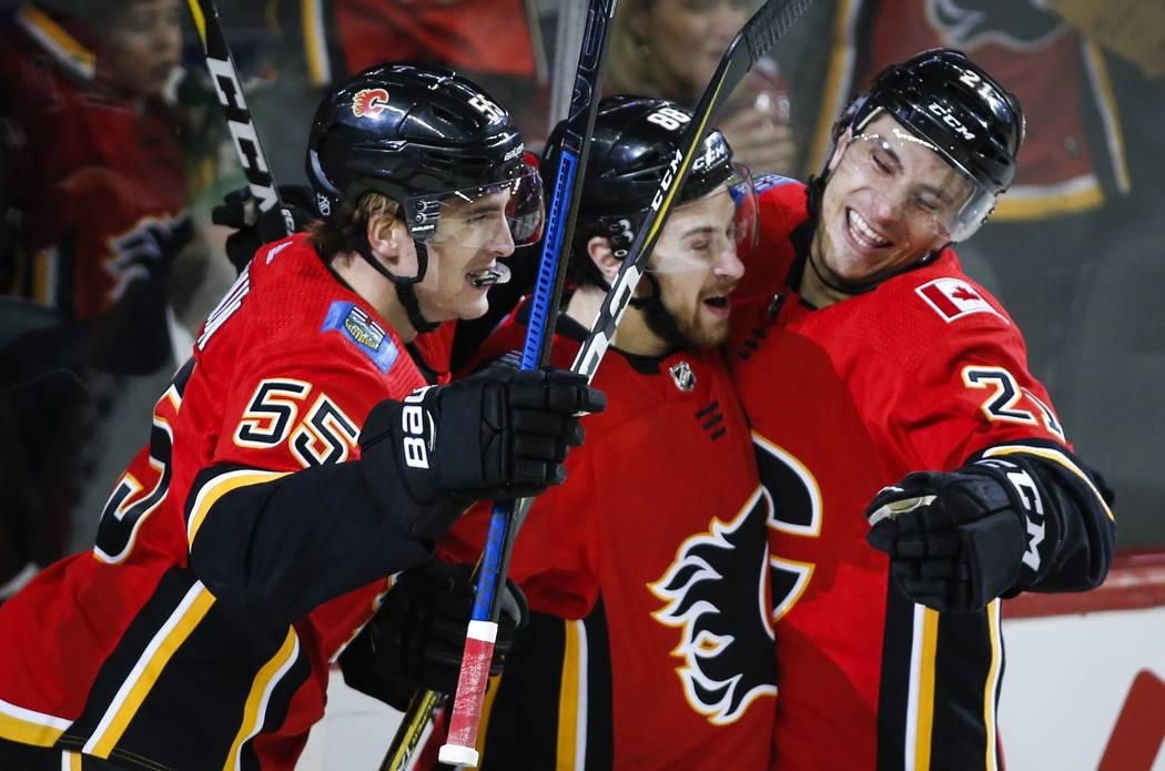 Andrew Mangiapane, centro de los Calgary Flames, celebra su gol con sus compañeros Noah Hanifin, a la izquierda, y Garnet Hathaway durante el primer período de acción de hockey de la NHL contra ...