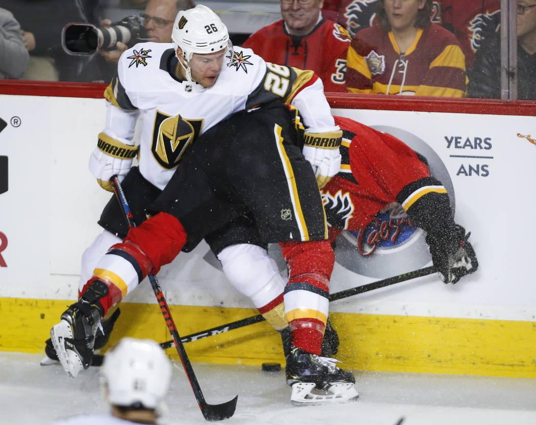 Paul Stastny, de los Golden Knights de Las Vegas, a la izquierda, sostiene a T.J. Brodie de los Calgary Flames en las tablas durante el primer período de acción de hockey de la NHL en Calgary, A ...