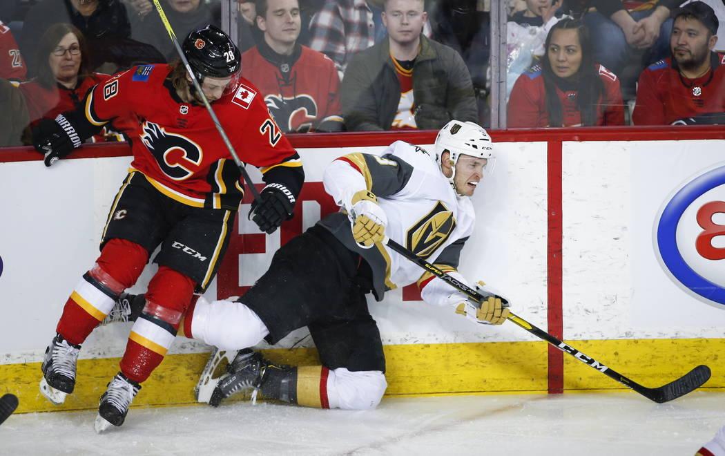 Brayden McNabb de los Vegas Golden Knights, a la derecha, es atacado por Elias Lindholm, de Suecia, de los Calgary Flames, durante el primer período de acción de hockey de la NHL en Calgary, Alb ...
