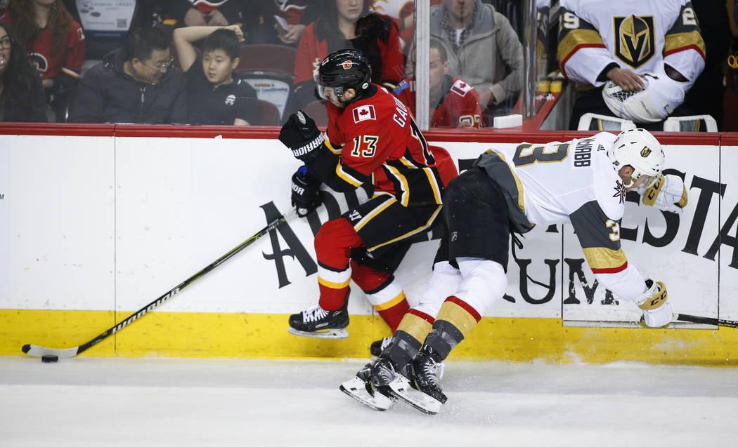 Brayden McNabb, de los Golden Knights de Las Vegas, a la derecha, empuja a Johnny Gaudreau de los Callgary Flames durante el primer período de acción de hockey de la NHL en Calgary, Alberta, el ...