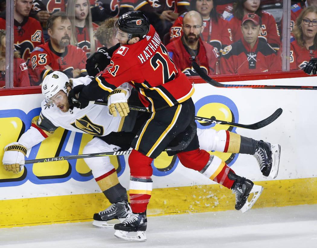 A Jon Merrill de los Vegas Golden Knights, a la izquierda, lo sostiene el Garnet Hathaway de los Calgary Flames durante el primer período de acción de hockey de la NHL en Calgary, Alberta, el do ...