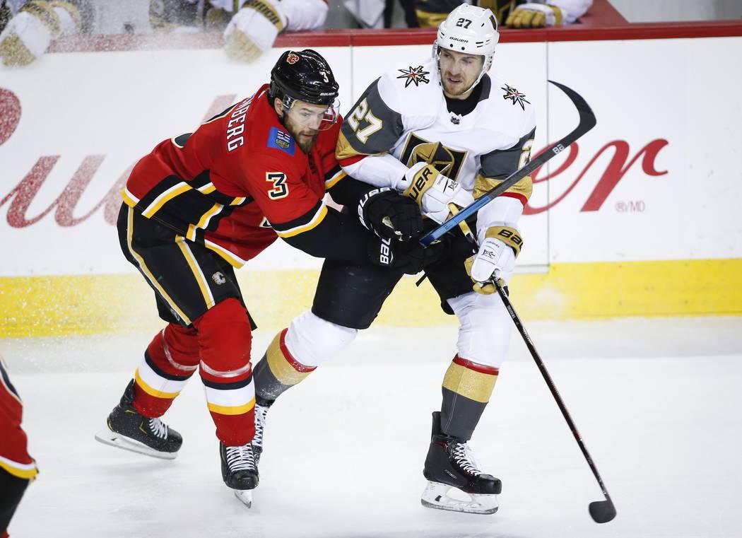 Shea Theodore de los Vegas Golden Knights , a la derecha, es atacado por Oscar Fantenberg de los Calgary Flames, de Suecia, durante el segundo período de acción de hockey de la NHL en Calgary, e ...