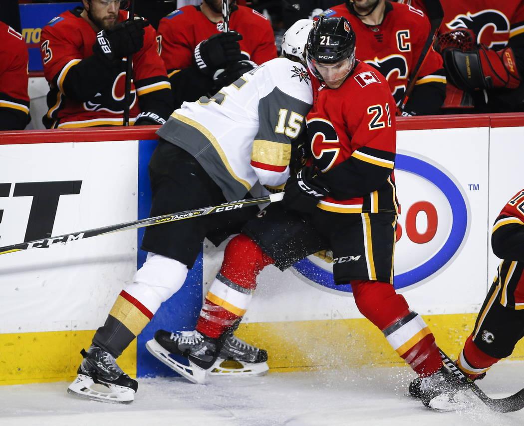 Jon Merrill de los Vegas Golden Knights, a la izquierda, controla a Garnet Hathaway de los Calgary Flames durante el tercer período de un juego de hockey de la NHL en Calgary, Alberta, el domingo ...