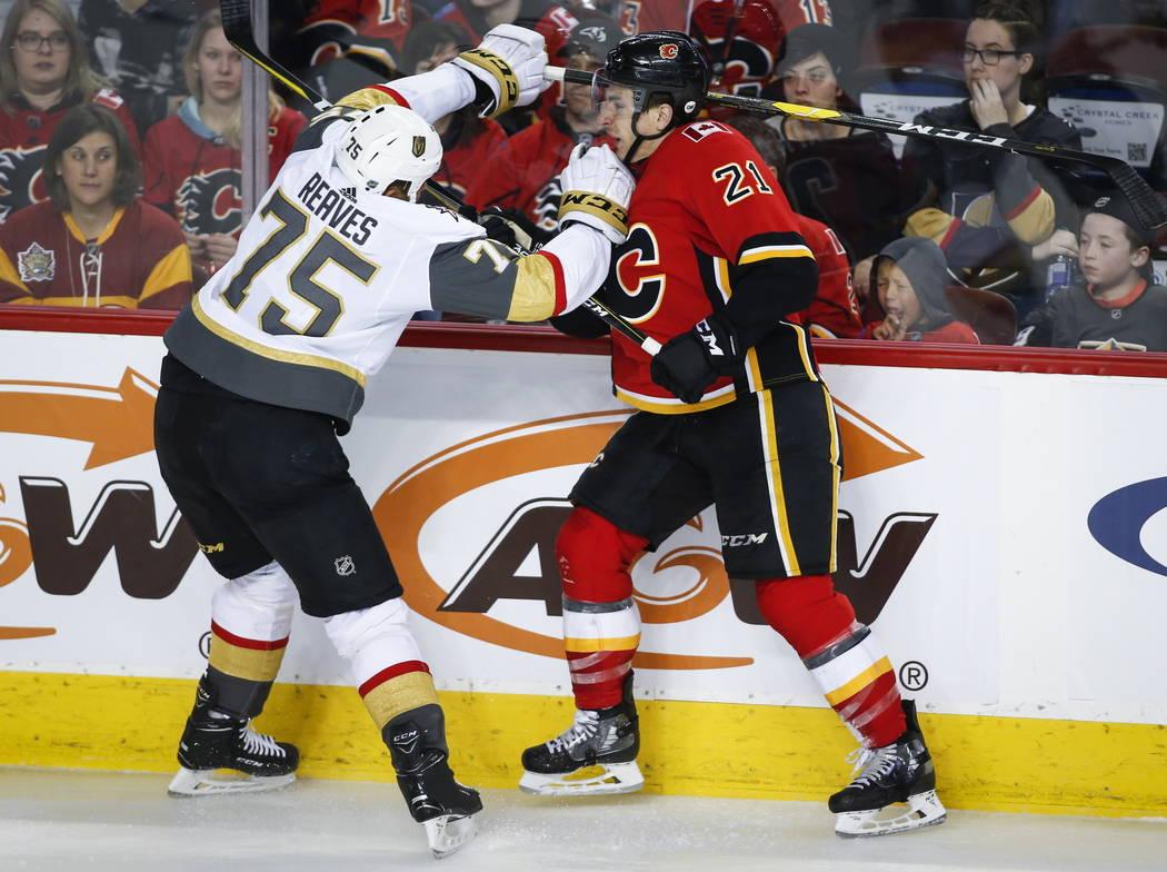 Ryan Reaves, de los Vegas Golden Knights, a la izquierda, controla a Garnet Hathaway de los Calgary Flames durante el tercer período de un juego de hockey de la NHL en Calgary, Alberta, el doming ...